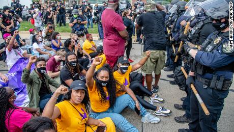 A group of demonstrators sat down in front of police during a march for Breonna Taylor in Louisville, Kentucky.