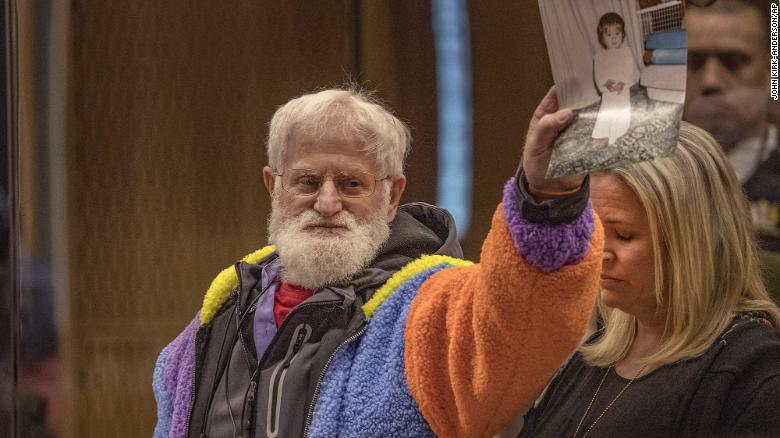 John Milne holds a photograph of his son, Sayyad Milne, who was killed in the attacks, during his victim impact statement in Christchurch, New Zealand, on August 26, 2020.