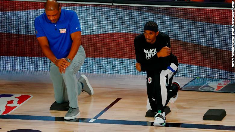 Rivers berlutut dengan Lou Williams selama lagu kebangsaan sebelum dimulainya pertandingan melawan Dallas Mavericks.
