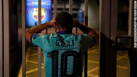 One Barcelona fan with the Greatest Of All Time on his shirt looks dejected outside the Camp Nou.