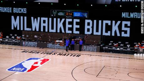 Referees stand on an empty court before the start of a scheduled game between the Milwaukee Bucks and the Orlando Magic for Game Five of the Eastern Conference First Round during the 2020 NBA Playoffs  August 26 in Lake Buena Vista, Florida.