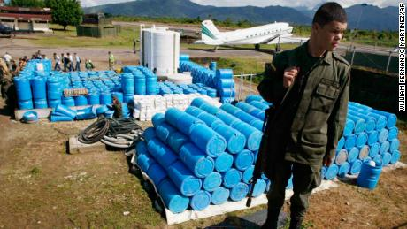 A police officer stand in front of herbicide containers at an anti-narcotic police base in Villa Garzon, near the southern Colombia's border with Ecuador, on Dec. 15, 2006.