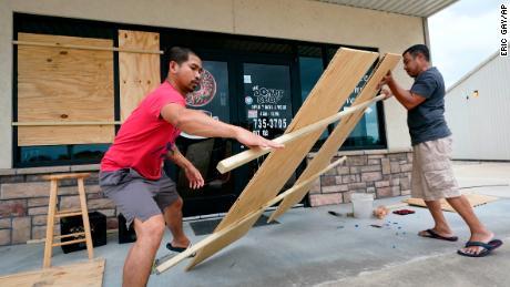 Daoith Porm, izquierda, y Bunsant Khov, derecha, abordan su negocio con el huracán Laura a solo unas horas de distancia.