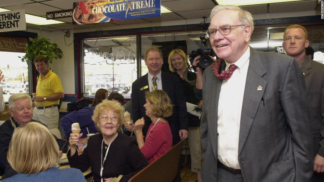 "Buffett arrives at an Omaha Dairy Queen to autograph books and chat with Berkshire Hathaway shareholders in 2002. Many people were in Omaha for Berkshire Hathaway's annual shareholders meeting, which has been described as ""the Woodstock of Capitalism."""