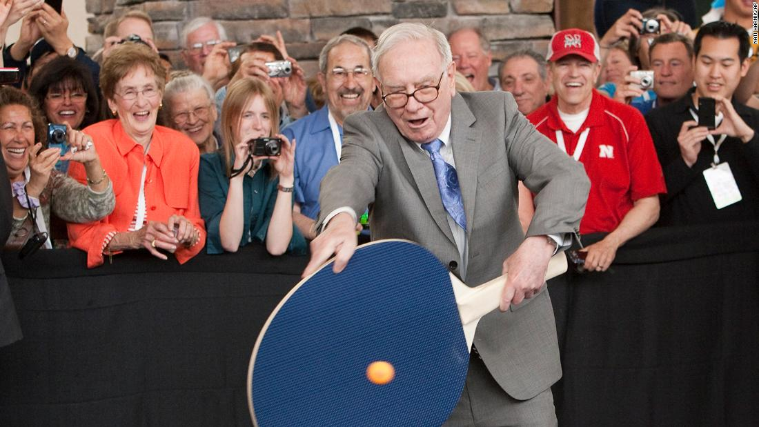 Buffett uses a large paddle to play table tennis in 2010.