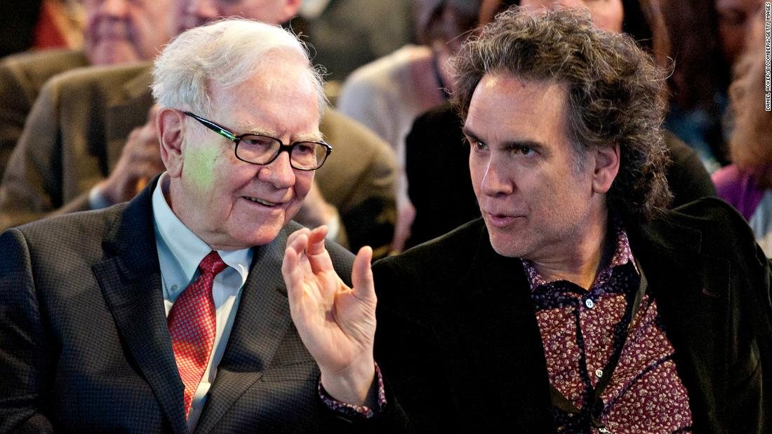 Buffett talks with his son Peter before the start of the shareholders meeting in 2011.
