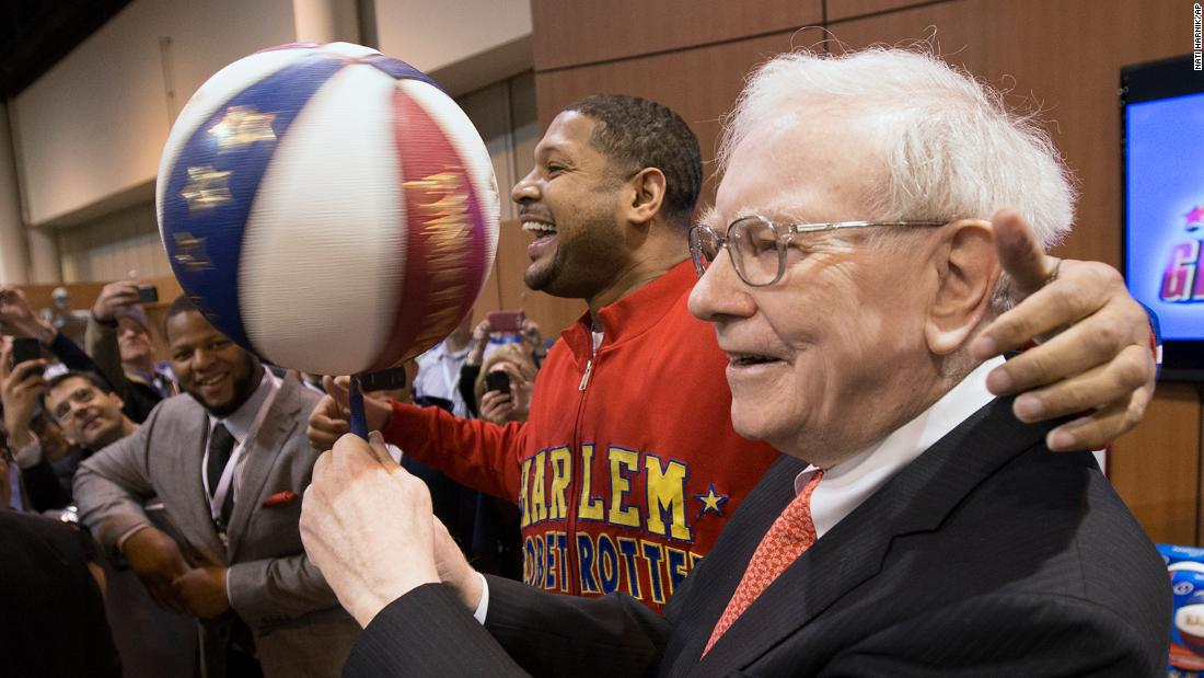 "Buffett spins a basketball with the help of Chris ""Handles"" Franklin, one of the Harlem Globetrotters, at the Berkshire Hathaway shareholders meeting in 2013. At left is football star Ndamukong Suh."