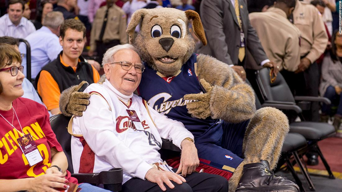 Buffett goofs off with Cleveland Cavaliers mascot Moon Dog prior to an NBA game in 2014.