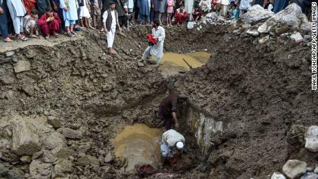 Villagers and rescuers search for bodies among debris after a flash floods in Parwan province, on August 26, 2020.