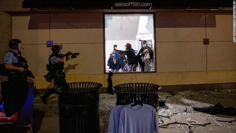 Police clear out and secure a Saks OFF 5th store in Minneapolis on August 26.