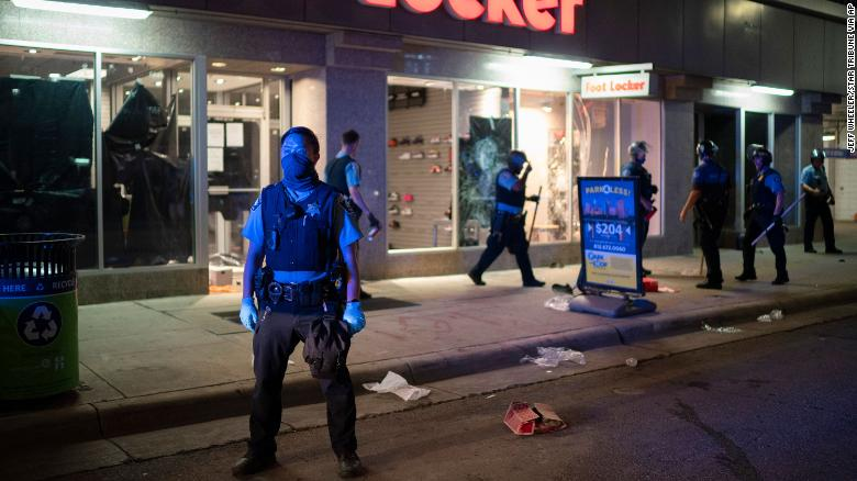Minneapolis Police stand outside a looted Foot Locker store on Wednesday, August 26.