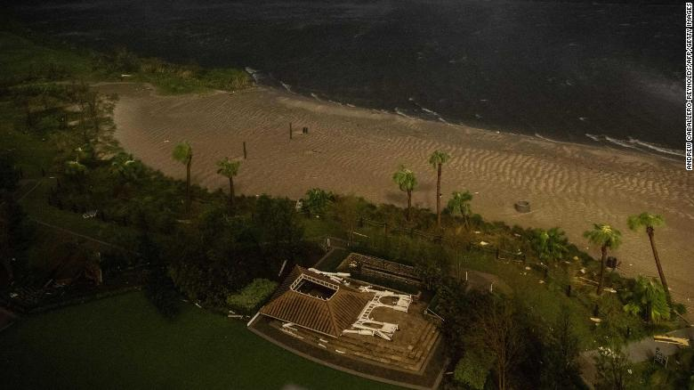 The remnants of a flattened building lie near a beach as the eye wall of Laura passes over Lake Charles, Louisiana.