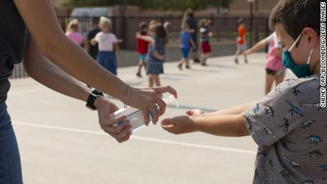 A teacher sprays hand sanitizer on a student's hands at an elementary school in Surprise, Arizona, on Aug. 20, 2020. The FDA is warning consumers about misleading packaging of hand sanitizers that look like food or drink.