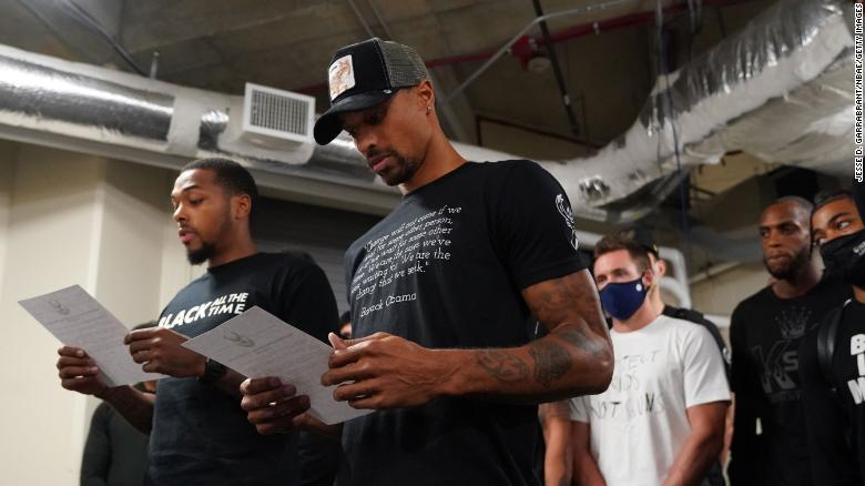 Sterling Brown and George Hill of the Milwaukee Bucks read a statement to the media on August 26.