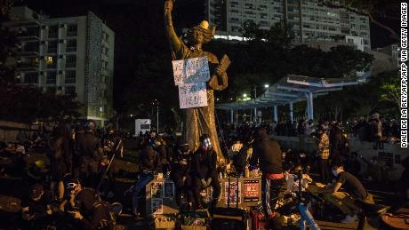 Protesters sit next to a Goddess of Democracy statue at the CUHK campus in Hong Kong on November 12, 2019.
