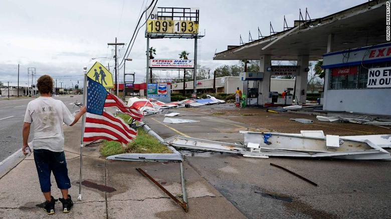 A man walks by debris at a Lake Charles gas station on Thursday.