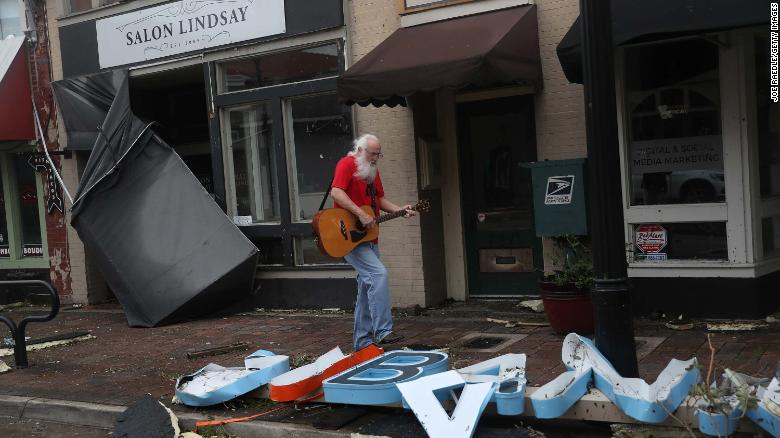 A man plays his guitar while walking through the downtown area of Lake Charles on Thursday.