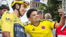 Colombia's Tour de France winner Egan Bernal (L) poses for a 'selfie' with a supporter from Colombia ahead of the start of the Acht van Chaam criterium cycling race in Chaam on July 31, 2019.