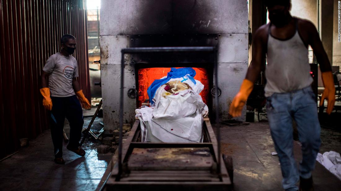 Workers in New Delhi prepare to cremate the body of a coronavirus victim on August 22.