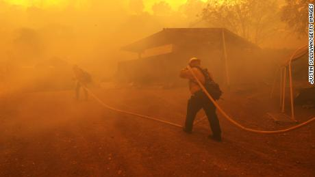 Firefighters carry a hose towards a burning structure as the LNU Lightning Complex Fire burns near Napa, California. This year, fewer inmates are able to help to fight the wildfires.
