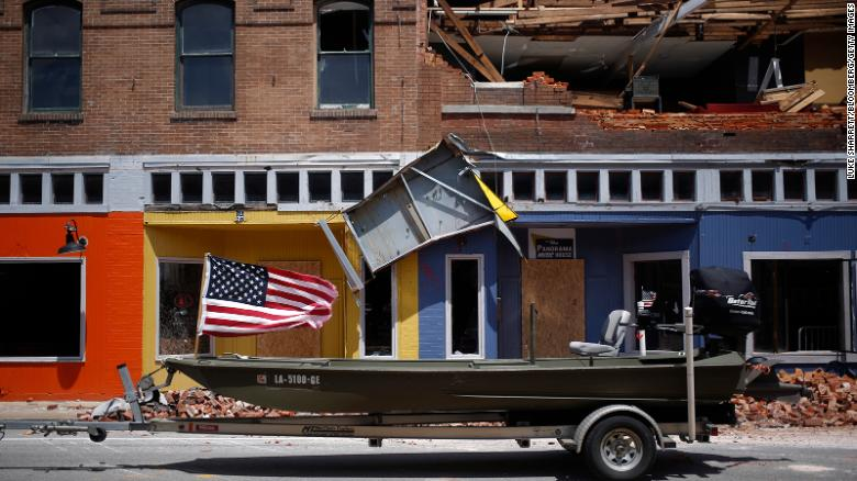 A U.S. flag flies on a boat parked in front of a damaged building after Hurricane Laura made landfall in Lake Charles, Louisiana, U.S., on Thursday