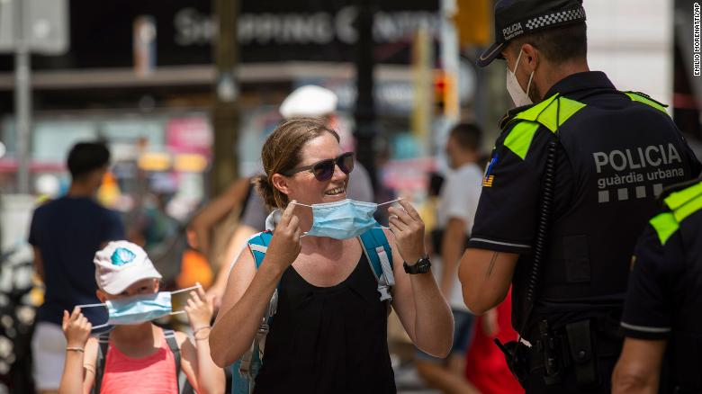 Catalonian police officers ask a woman to wear a face mask at Las Ramblas in Barcelona, Spain, on July 9, 2020.