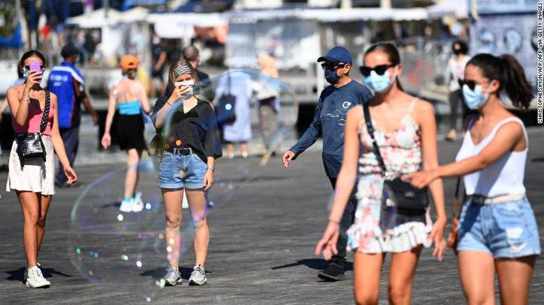 People wearing face masks stroll in the old harbour of Marseille on Wednesday.