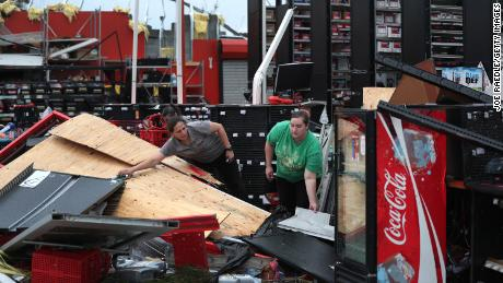 Rachel Ellis (left) and J'Nay Fitch salvage items from the AutoZone store where they worked in Lake Charles, Louisiana. Hurricane Laura ripped the roof off the store.