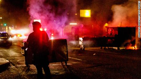 People protesting police brutality spray graffiti and start fires at the Portland Police Union building on Friday.