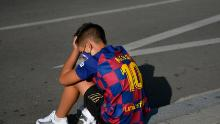 A disappointed young Barcelona supporter sporting Lionel Messi's jersey sits on the pavement outside the Barcelona training ground hoping for a glimpse of his hero.