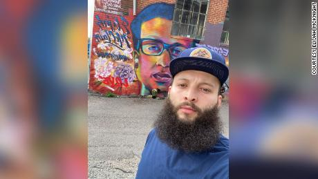 Elijah McKnight stands in front of a mural to Elijah McClain. Both encountered law officers and were injected with ketamine.