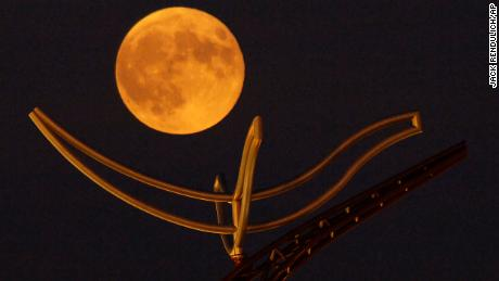 "A full ""corn moon"" rises above a large metal sculpture on the campus of the University of Minnesota, Duluth."