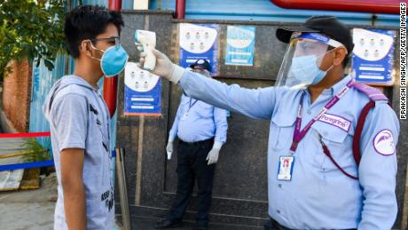 A student gets their temperature taken at an examination center in Noida, India.
