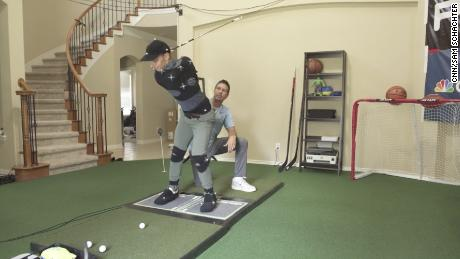 Como helps one of his teaching assistant's with his swing.
