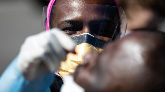 A doctor administers a COVID-19 swab test on a person in a parking lot. (AP Photo/Matt Rourke)