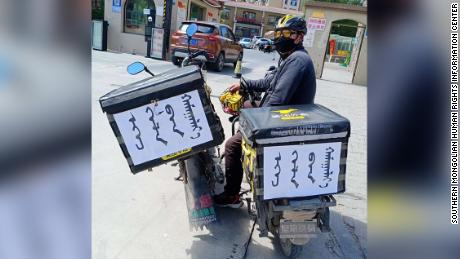 "Some food delivery workers in Inner Mongolia have stuck signs reading ""save our mother tongue"" on their bikes."
