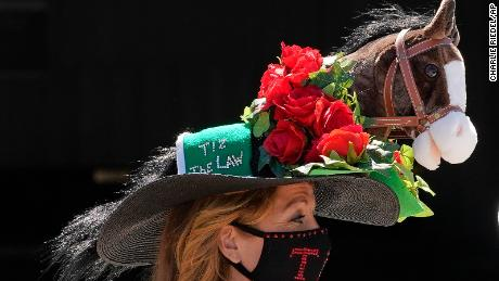 A guest wearing a Tiz the Law-themed hat stands in the paddock before the race.