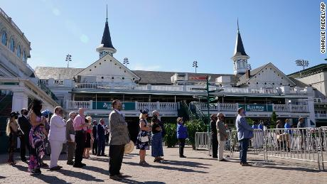 A few guests stand during the nation anthem before the  running of the Kentucky Derby on Saturday. Few people were allowed inside because of health concerns.