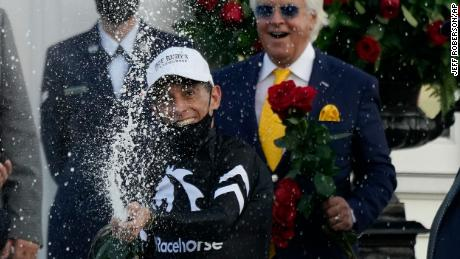 Jockey John Velazquez celebrates after riding Authentic to victory at the Kentucky Derby as Bob Baffert watches from behind. Velazquez has now ridden three Derby winners.