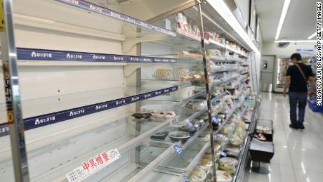 A man shops near empty food shelves at a convenience store in Hitoyoshi, Kumamoto Prefecture on September 6, as evacuation advisories are issued due to the approach of Typhoon Haishen.