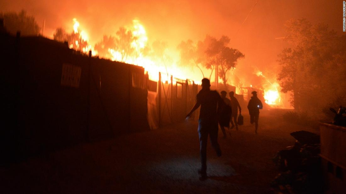 Refugees and migrants flee as the fire spreads through Moria.