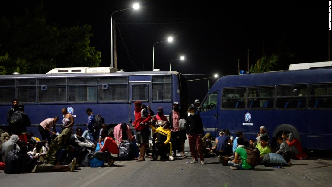 Camp evacuees try to reach the port of Mytilene as police block a road during the fire.