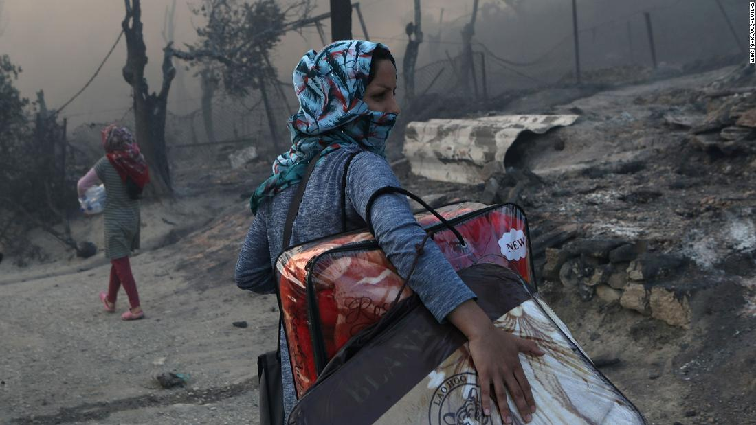 A woman carries her belongings in the aftermath of the fire.