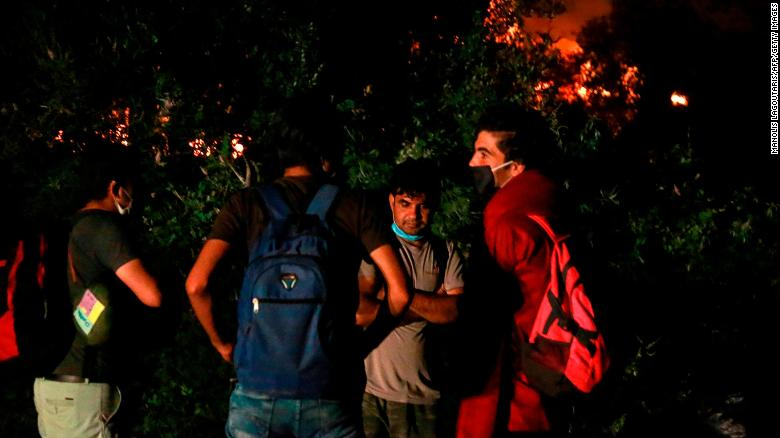 Migrants stand outside the Moria camp on the island of Lesbos as a major fire ravages the site.