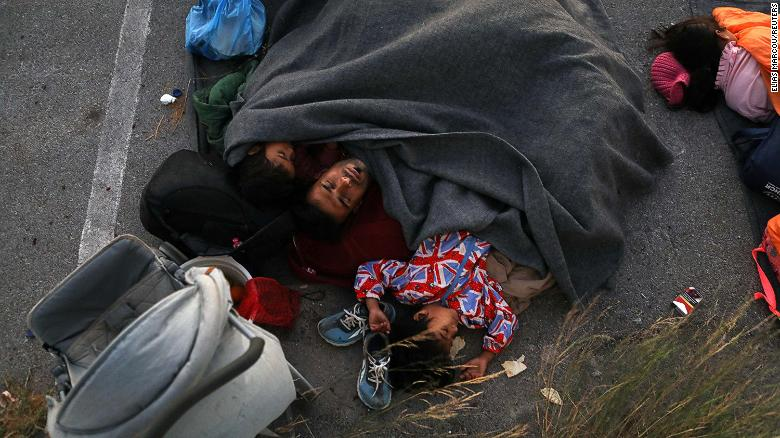 A family sleeps at a parking space, following the fire at the Moria camp.
