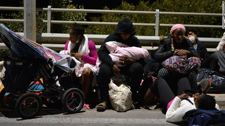 Refugees and migrants with their children gather on a bridge on Wednesday after the fire at the Moria refugee camp.