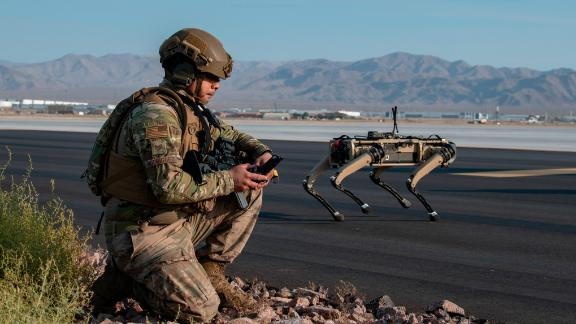 Tech. Sgt. John Rodiguez, 321st Contingency Response Squadron security team, provides security with a Ghost Robotics Vision 60 prototype at a simulated austere base during the Advanced Battle Management System exercise on Nellis Air Force Base, Nevada, Sept. 1, 2020. The ABMS is an interconnected battle network - the digital architecture or foundation - which collects, processes and shares data relevant to warfighters in order to make better decisions faster in the kill chain. In order to achieve all-domain superiority, it requires that individual military activities not simply be de-conflicted, but rather integrated -- activities in one domain must enhance the effectiveness of those in another domain. (U.S. Air Force photo by Tech. Sgt. Cory D. Payne)