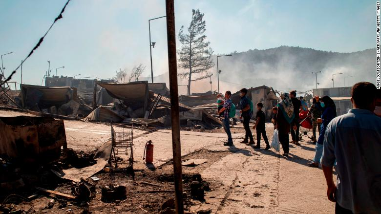 Migrants walk in the burnt camp of Moria on the island of Lesbos on Wednesday after a major fire broke out.