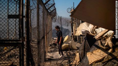 A girl stands amid rubble in the burnt camp after the fires Greek authorities believe were lit by residents.