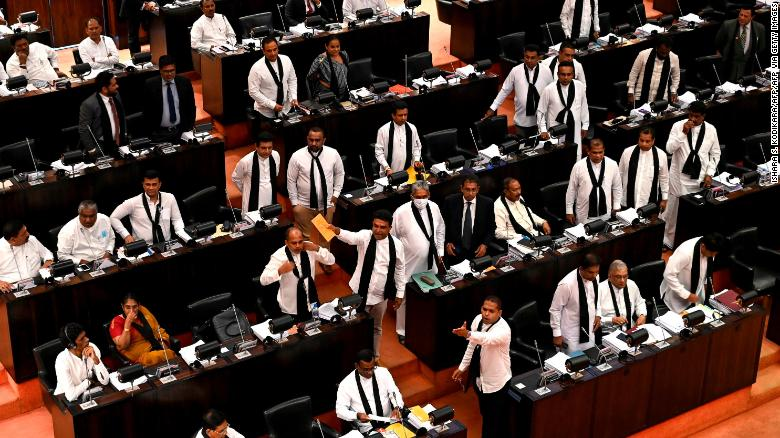Sri Lankan opposition legislators, wearing black shawls, protest in parliament as convicted murderer Premalal Jayasekara is sworn in.